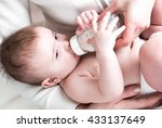 the baby in diapers eating milk ... | Shutterstock . vector #433137649
