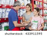 Stock photo family looking at salesman using digital tablet in pet store 433911595