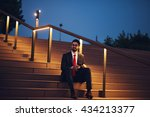 Handsome businessman sitting on the stairs and working at night. High ISO