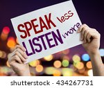 Small photo of Speak Less Listen More placard with night lights on background