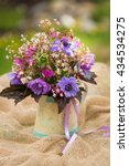 Small photo of Garden style summer bouquet. Mix of lilac and purple anemone flowers, geranium flowers and heuchera or alumroot leaves. Bouquet on sackcloth background in decorative pot. Garden style wedding bouquet