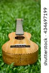 Small photo of Mango wood Ukulele on grass
