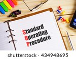"""Small photo of """"Standard Operating Procedure"""" text on paper in open diary with spectacles, colourful push pin, pen and calculator on the wooden table - business and finance concept"""