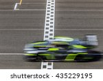 Small photo of Race car racing on speed track with motion blur crossing finish line
