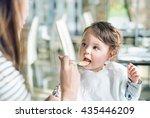mum spoon feeds her child | Shutterstock . vector #435446209