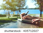 Stock photo girls hands with pen writing on notebook in park 435712027