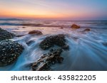 Small photo of Sea waves crashing over rocks on the wild stone beach in sunset time and seafoam created by the agitation of seawater in the moment of ocean waves crashing against rocks.