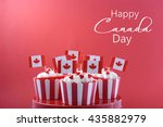 Small photo of Happy Canada Day Party Cupcakes on a red cake stand with maple leaf flags on a white wood table and red background.