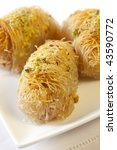 Kadayif, or Middle Eastern cakes with pistachios and honey.  Similar to baklava, sticky and sweet. - stock photo