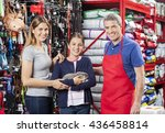 Stock photo girl holding rabbit with mother and salesman in store 436458814