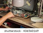 Small photo of Technician repairing a television. Hand with voltmeter above board with components. Repair of circuits electric equipment, close up