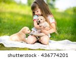 Stock photo little girl with a golden retriever puppy a puppy in the hands of a girl 436774201