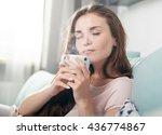 Young Woman Sitting On Couch A...
