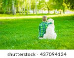 Stock photo child hugging golden retriever sitting with his back to the camera 437094124