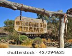 "Small photo of old vintage wood signboard with text "" welcome to Adama"" hanging on a branch"