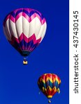 Small photo of Several brightly colored hot air balloons aloft in early morning blue sky