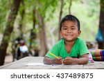 Small photo of Asian cute little boy(poor kids) is drawing,painting with color pencil and study at old home.Homeless poor children,smile,lying on dirty wooden table and writing or coloring picture on books.