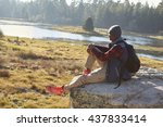 Young Black Man Sitting Alone...