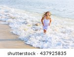 Small photo of beautiful blonde teenage girl wearing flowy white dress standing ankle dee in ocean water