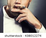 Close-up hand of bearded caucasian man smoking a cigar. Wearing grey suit and white shirt. Studio portrait on gradient black to grey background. Toned