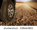 Car Tire On Dirt Road At Sunse...