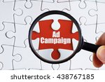 """Small photo of """"Ad campaign"""" text on red missing jigsaw puzzle with man right hand hold black magnifying glass searching for missing puzzle peace - business and finance concept"""