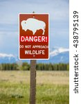 Small photo of Sign warning danger of wildlife bison buffalo approaching roadside along pasture and mountain view landscape scenic tetons national park