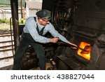 Small photo of JESENICE, SLOVENIA - JUNE 11th 2016: Sooty stoker shoveling coal in the furnace of the steam engine. Train is carrying tourists on the old Bohinj railway.
