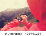 Small photo of young woman hiker checking the altimeter on sports watch at mountain peak