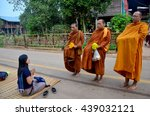 Small photo of SAKON NAKHON, THAILAND - JANUARY 16 : Tradition of almsgiving with sticky rice by Monks procession walk on the road for people put food offerings on January 16, 2016 in Sakon Nakhon, Thailand