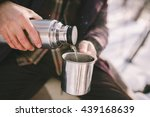 Man Pours Tea From A Thermos....