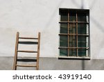 Old wooden stair against the wall of a old house with a window on the right - stock photo