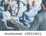 Business coach. Rear view of man gesturing with hand while standing against defocused group of people sitting at the chairs in front of him