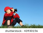 Boy looks into binoculars on top of hill - stock photo