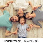 Small photo of Top view of beautiful young parents, their cute little daughter and son holding hands, looking at camera and smiling, lying on wooden floor