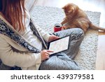 Stock photo woman sitting on the carpet near the sofa using a tablet with headphones drinking coffee from a red 439379581