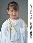 Small photo of Little child (girl age 6) who wants to be a physician play pretend to be medical doctor in ambulatory care clinic looks at the camera.Medical concept with copy space.