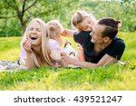 family lying on grass in... | Shutterstock . vector #439521247