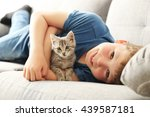 Stock photo child with kitten on grey sofa at home 439587181