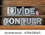 Small photo of divide and conquer phrase made from metallic letterpress type on wooden tray
