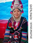 Small photo of TACHILEIK, MYANMAR (BURMA) - DECEMBER 23, 2009: A young Akha woman in ceremonial dress smiles as she prepares to perform on stage at a festival.