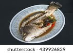 Small photo of Eat all steamed snapper with soy sauce is delicious on dish, steamed snapper with soy sauce with grounded port, mushroom, ginger, chili and garlic on black background or isolate