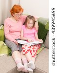 Small photo of Grandmother teach grandchild to read aloud, they sitting on couch and plaid, girl holding book and read it aloud and smile