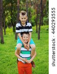 Small photo of Gymnastic acrobatic pyramid of two brothers on the green trees background. Happy kids having fun in summer park. Portrait of people outdoors. Funny moment, laugh, smile.