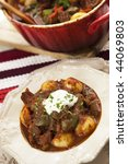 Traditional Hungarian goulash or beef stew, served from red crock pot. - stock photo