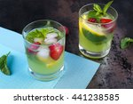 Small photo of Berry and lemon mojito cocktail with mint and ice in a glass. Two portions of fruit lemonade on a table on blue napkin. Lighting summer drink. Alcoholic drink in the bar or cafeteria.