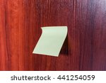 Small photo of Yellow adhesive sticker on a dark lackered wooden background. A piece of paper taped to the surface of a table or wall