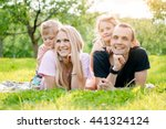 family lying on grass in... | Shutterstock . vector #441324124