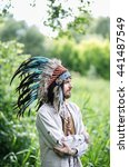Small photo of The young man in the national headdress war bonnet in the summer the forest, reflection, solitude, choices