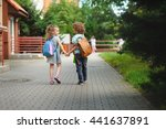 Small photo of Back to school. Two young students go to school hand in hand. They about something briskly talk. Behind the back of everyone satchel. Little first graders. Schoolchildren.